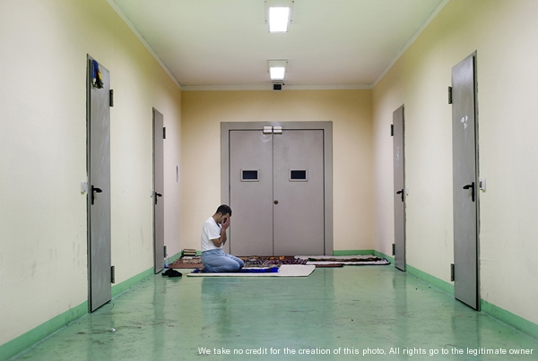 Bari, Italy - December 19, 2012 - Muslim immigrant prays in a corridor of the detention center of Bari Palese.Ph.Giulio Piscitelli